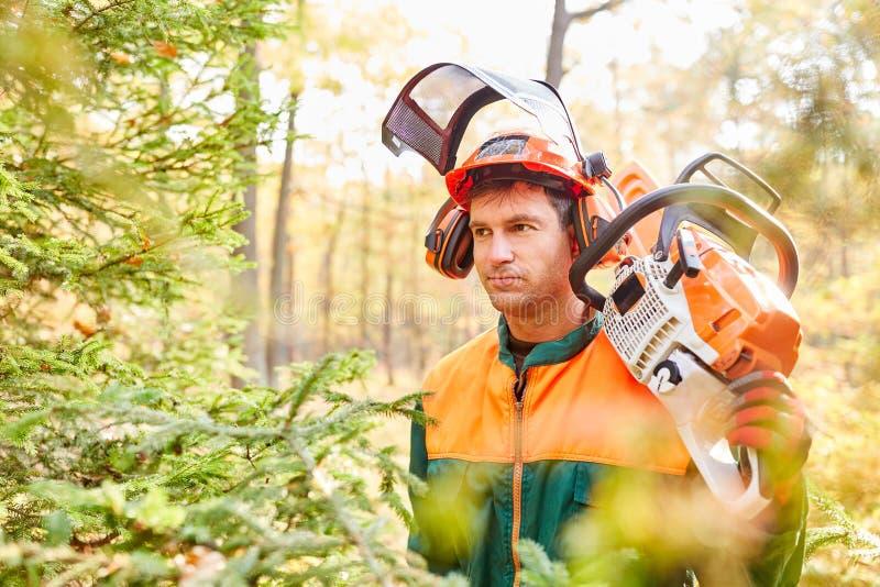 Uomo come un proprietario e boscaiolo della foresta in ingranaggio protettivo fotografia stock