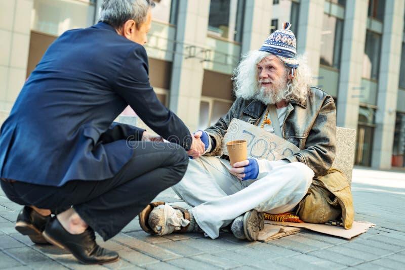 Uomo complementare che parla con fuggitivo povero immagine stock libera da diritti