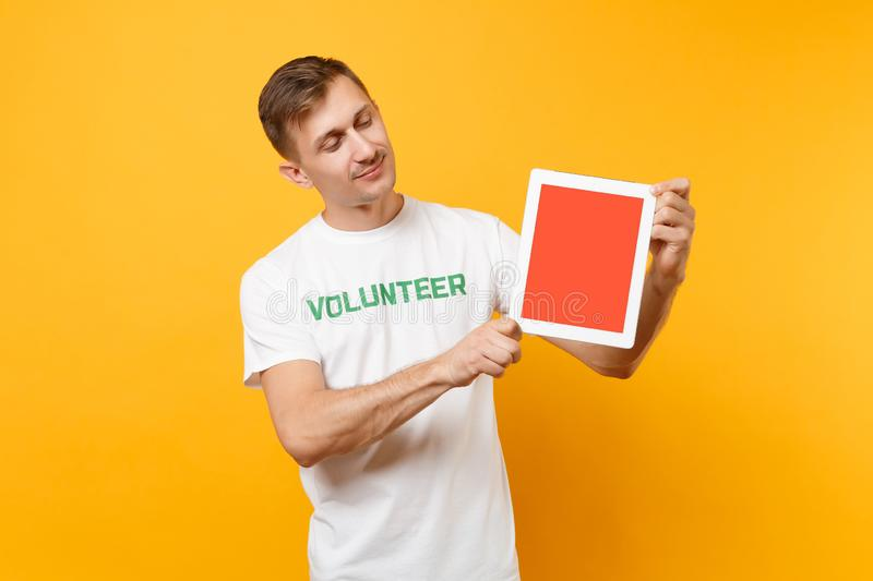 Uomo in computer volontario del pc della compressa della tenuta di titolo di verde dell'iscrizione scritto maglietta bianca con l fotografia stock