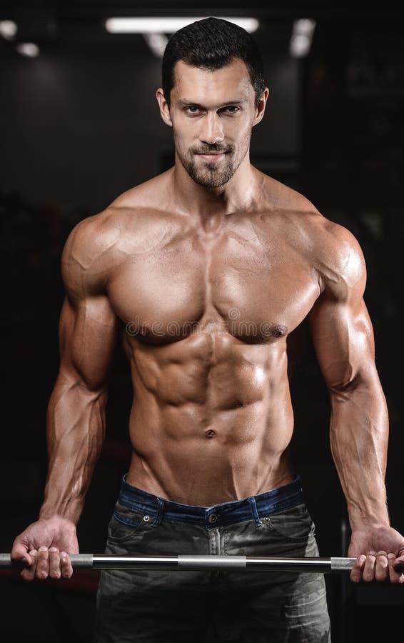 Uomo con addestramento del peso nel club di sport dell'attrezzatura della palestra immagini stock