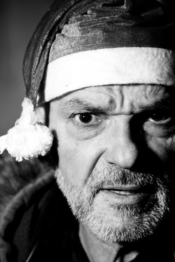 Uomo con Babbo Natale che vista frontale, foto in bianco e nero, con espressione arrabbiata, Natale sta arrivando immagini stock