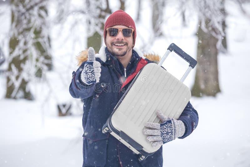 Uomo con bagagli contro il fondo di inverno fotografie stock