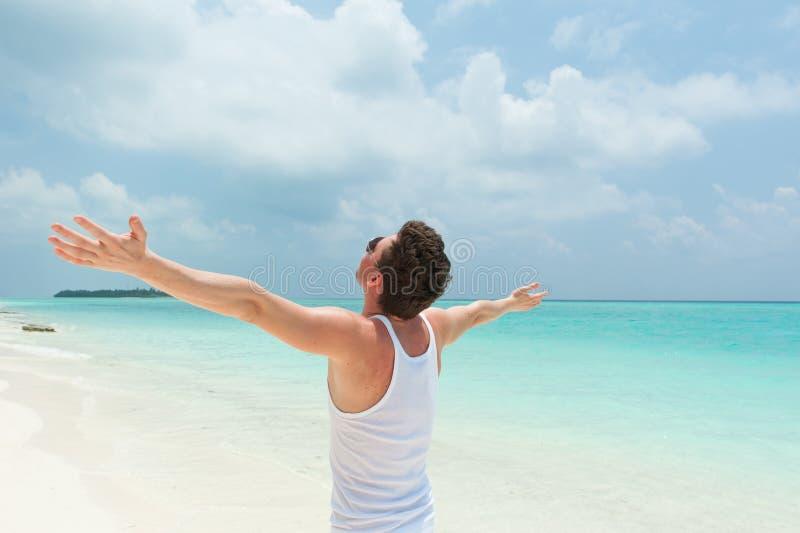 Uomo con a braccia aperte sopra la spiaggia, Maldive fotografia stock