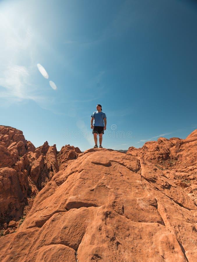 Uomo con camicie blu e costumi neri in piedi sulla cima delle formazioni Brown Rock sotto il cielo limpido immagini stock libere da diritti