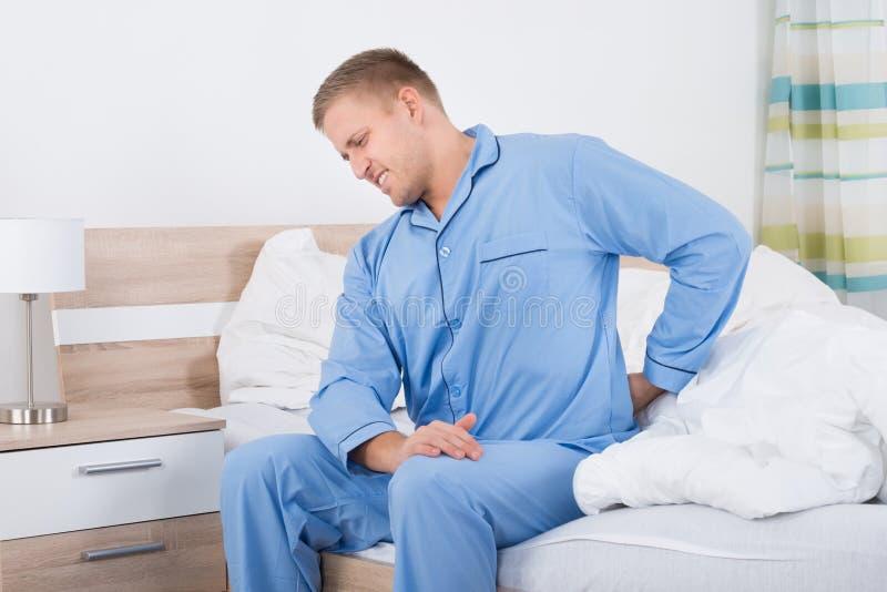 Uomo con dolore alla schiena che si siede sul letto immagine stock