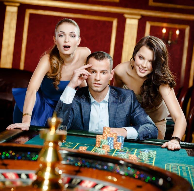 Uomo con due ragazze che giocano roulette al club del casinò fotografia stock libera da diritti