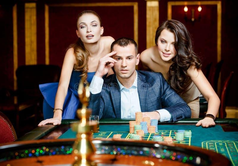 Uomo con due signore che giocano roulette al casinò fotografie stock