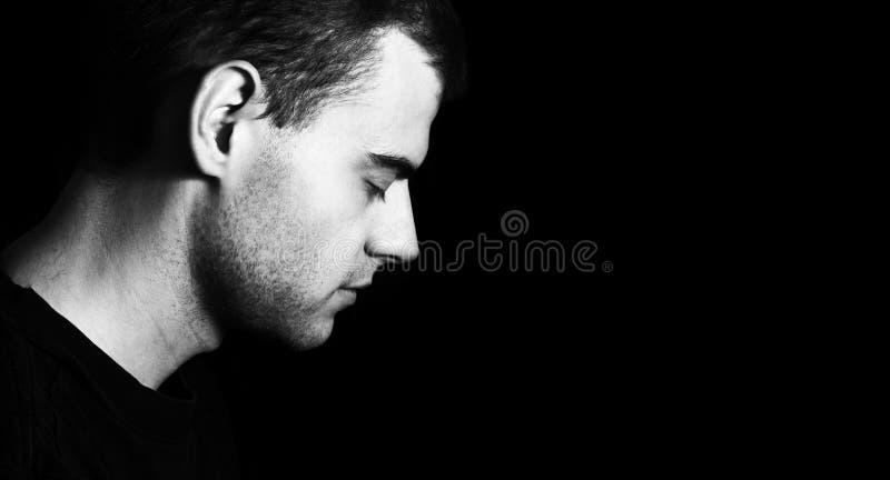 Uomo con gli occhi chiusi su un fondo nero immagini stock libere da diritti