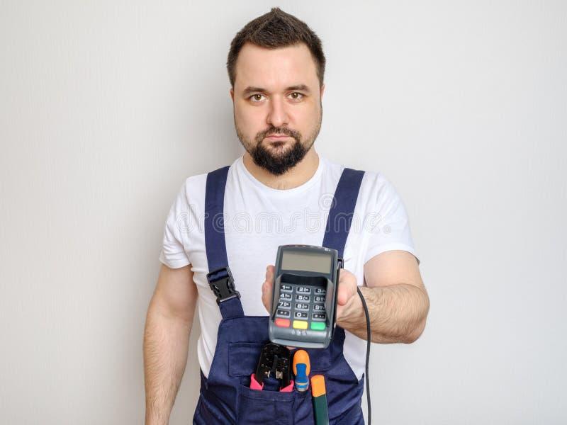 Uomo con gli strumenti che tengono il terminale di pagamento della banca fotografia stock libera da diritti