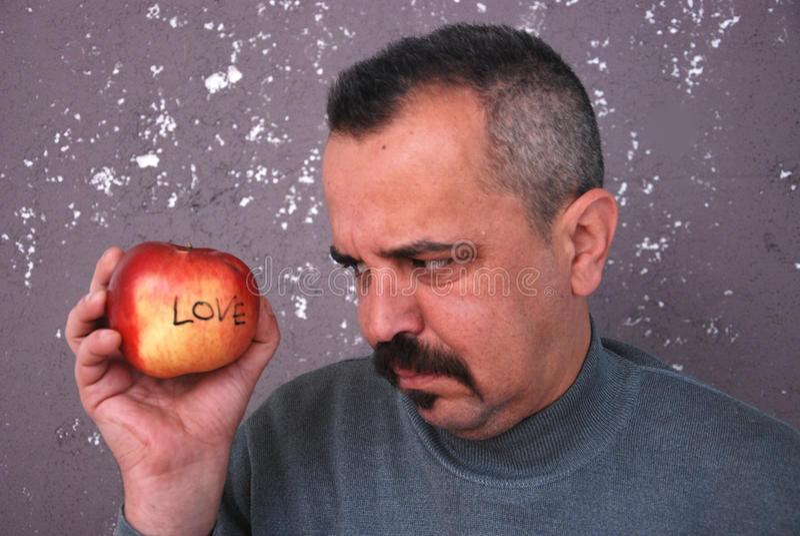 Uomo con i baffi che guardano la mela del biglietto di S. Valentino fotografie stock