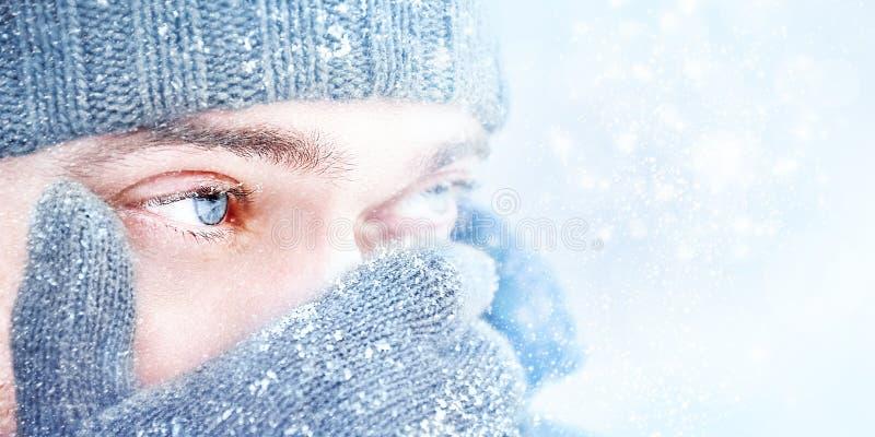 Uomo con i bei occhi azzurri contro un fondo di neve di caduta Bello tempo nevoso nevicare Fuoco selettivo immagini stock libere da diritti
