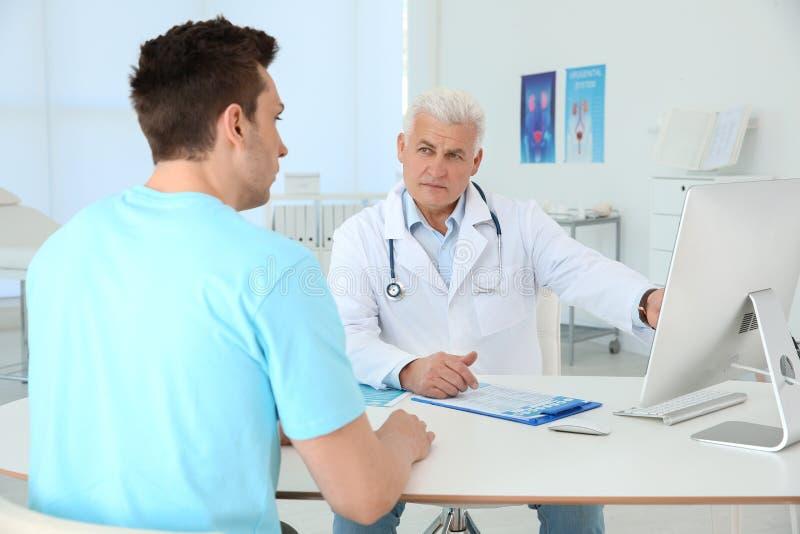 Uomo con i problemi sanitari che visita urologo immagine stock