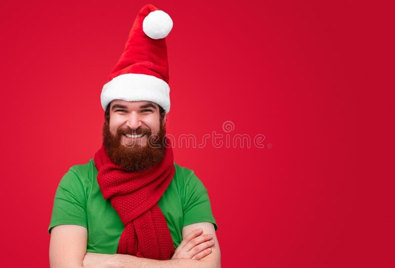 Uomo con i vestiti d'uso dell'elfo di natale della barba che sorride sopra il fondo rosso immagine stock