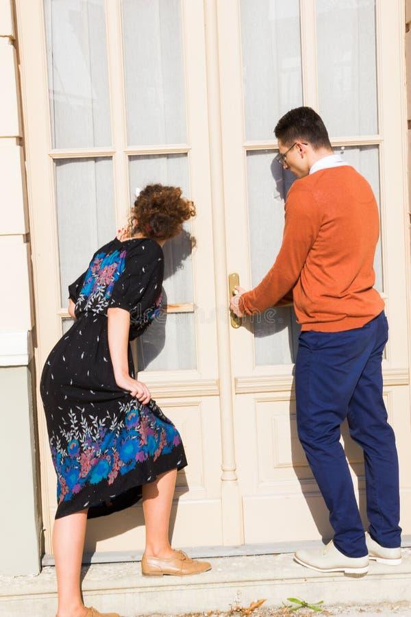 Uomo con i vetri nel maglione arancio con la donna che prova al ope immagine stock
