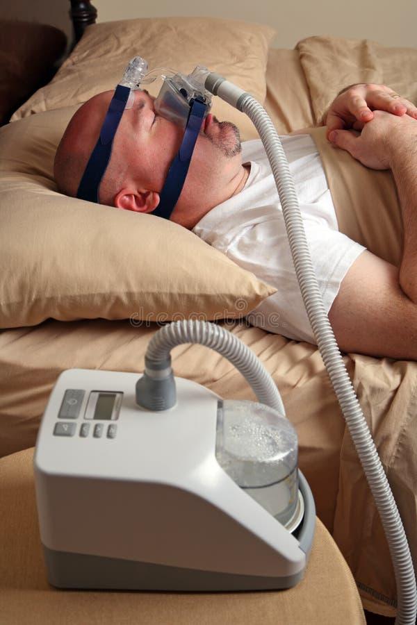 Uomo con il apnea di sonno per mezzo di una macchina di CPAP immagini stock libere da diritti
