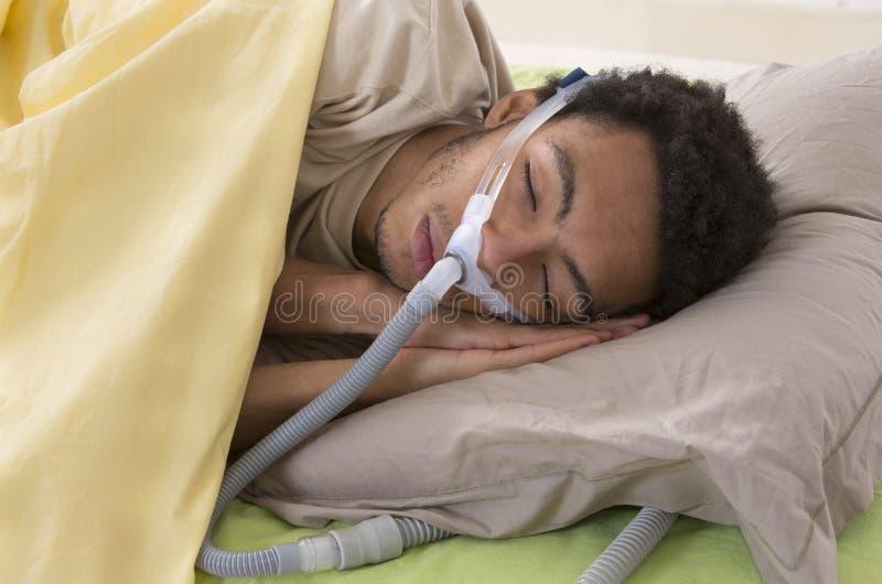 Uomo con il apnea di sonno per mezzo di una macchina di CPAP fotografia stock