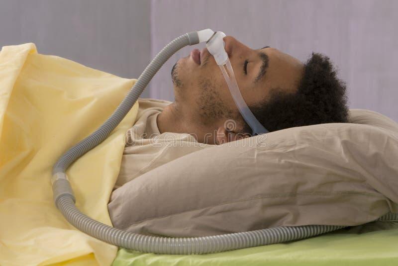 Uomo con il apnea di sonno per mezzo di una macchina di CPAP immagini stock