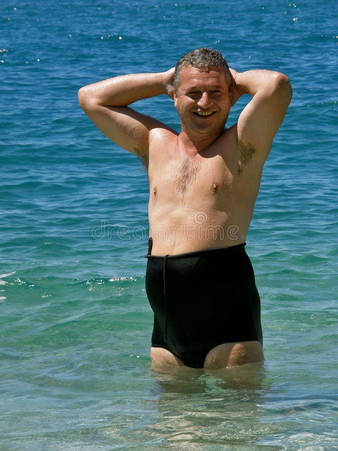 Uomo con il bikini di modo sul mare blu fotografia stock libera da diritti