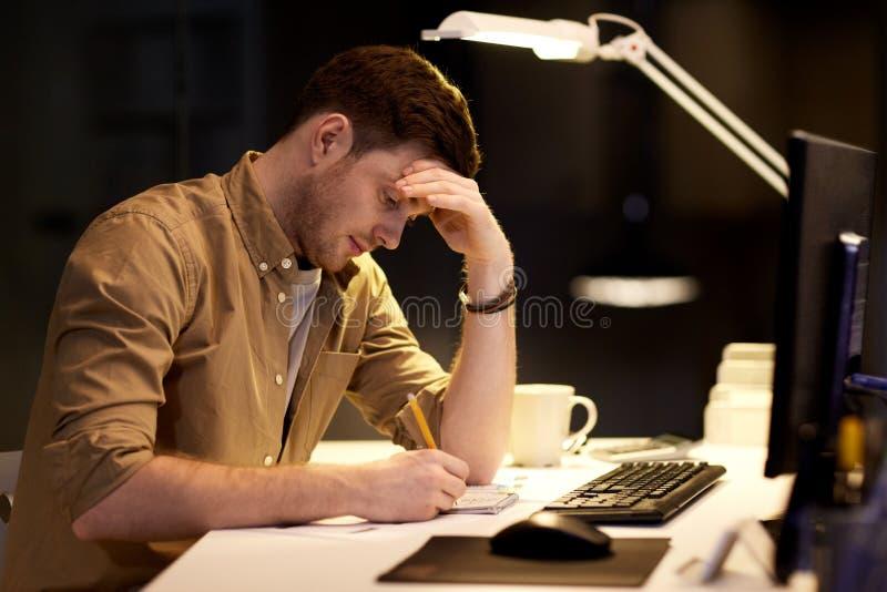 Uomo con il blocco note che funziona tardi all'ufficio di notte fotografia stock libera da diritti