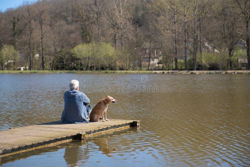 Uomo con il cane sulla fase di atterraggio immagine stock