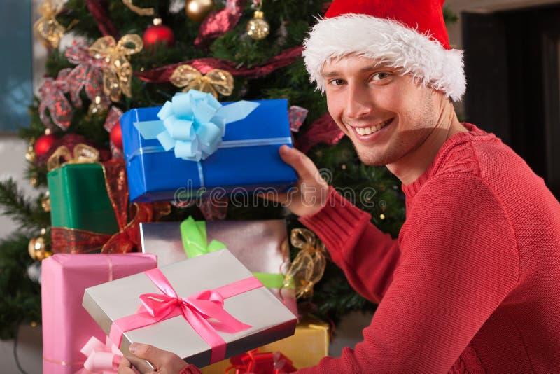 Uomo con il cappello di Santa che lascia i regali immagini stock