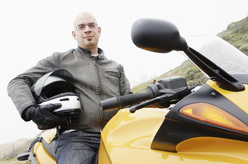 Uomo con il casco underarm che si siede su una motocicletta fotografia stock