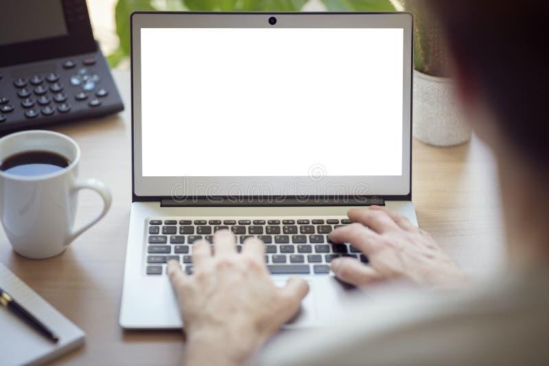 Uomo con il computer portatile alla scrivania con lo schermo in bianco fotografie stock