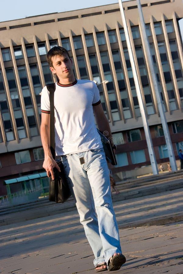 Uomo con il computer portatile che cammina lungo la via immagine stock