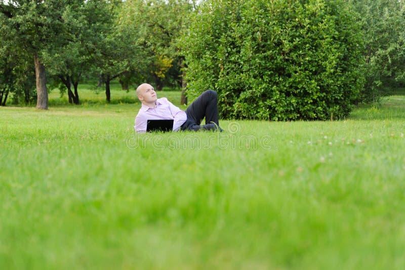Uomo con il computer portatile che si trova sull'erba verde fotografia stock