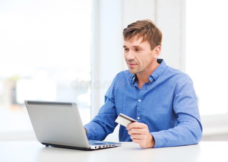 Uomo con il computer portatile e la carta di credito a casa immagini stock libere da diritti