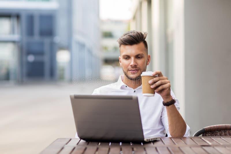 Uomo con il computer portatile ed il caffè al caffè della città fotografie stock libere da diritti