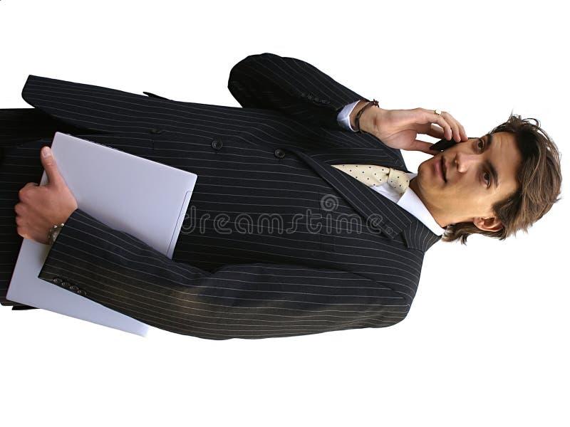 Uomo con il computer portatile ed il telefono mobile fotografie stock