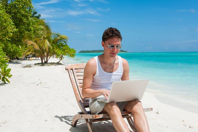 Uomo con il computer portatile sulla spiaggia immagine stock libera da diritti