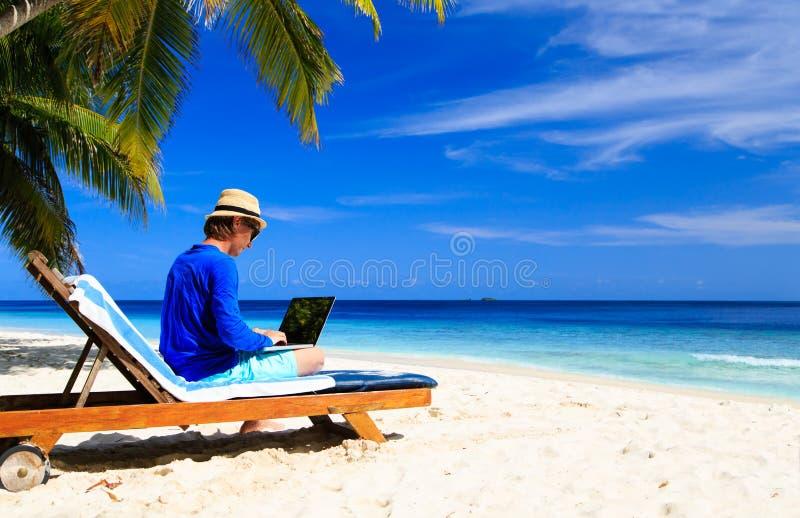 Uomo con il computer portatile sulla spiaggia tropicale fotografia stock libera da diritti