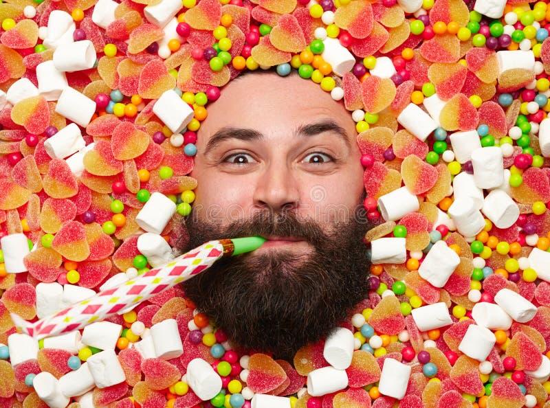 Uomo con il corno del partito in caramelle fotografia stock libera da diritti