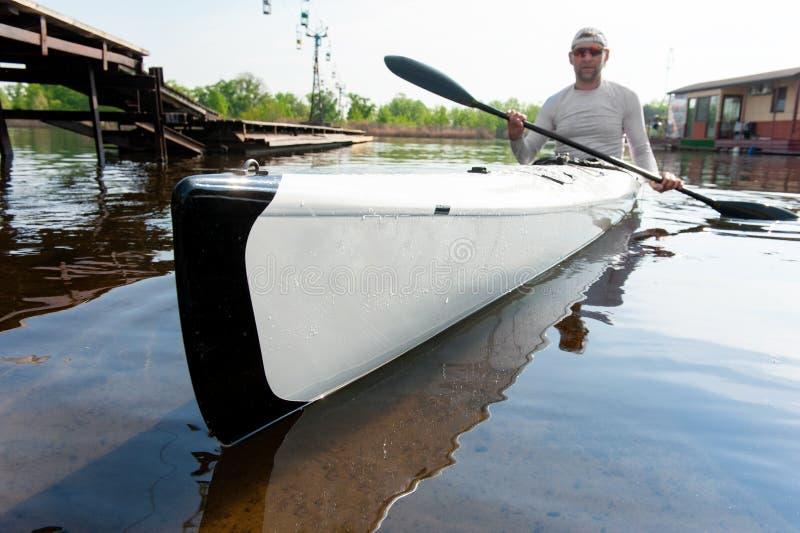 Uomo con il crogiolo della canoa e di remo vicino al pilastro fotografia stock libera da diritti