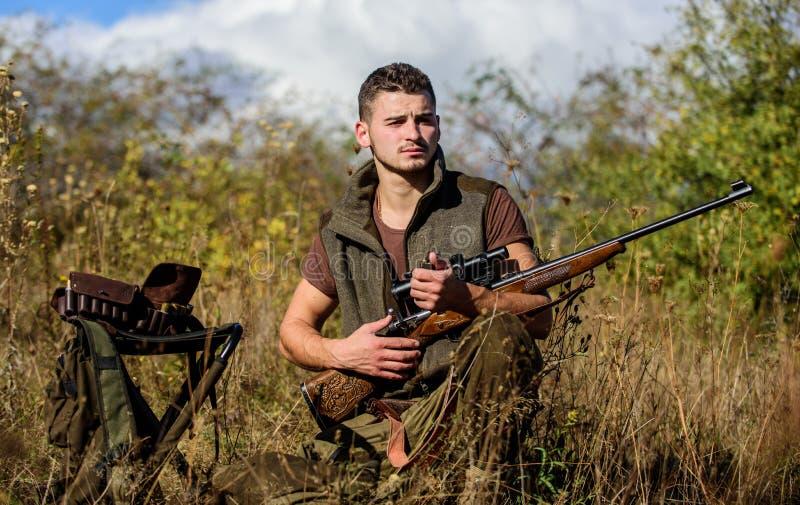 Uomo con il fondo della natura dell'attrezzatura di caccia del fucile Prepari per cercare Dovreste che cosa l'attimo che cercate  immagine stock libera da diritti