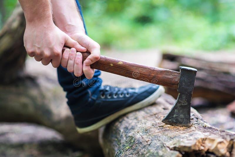 Uomo con il legno di taglio dell'ascia fotografia stock