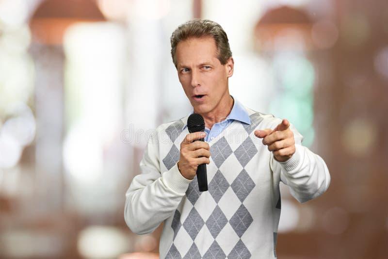 Uomo con il microfono che mostra in avanti con il dito fotografia stock libera da diritti