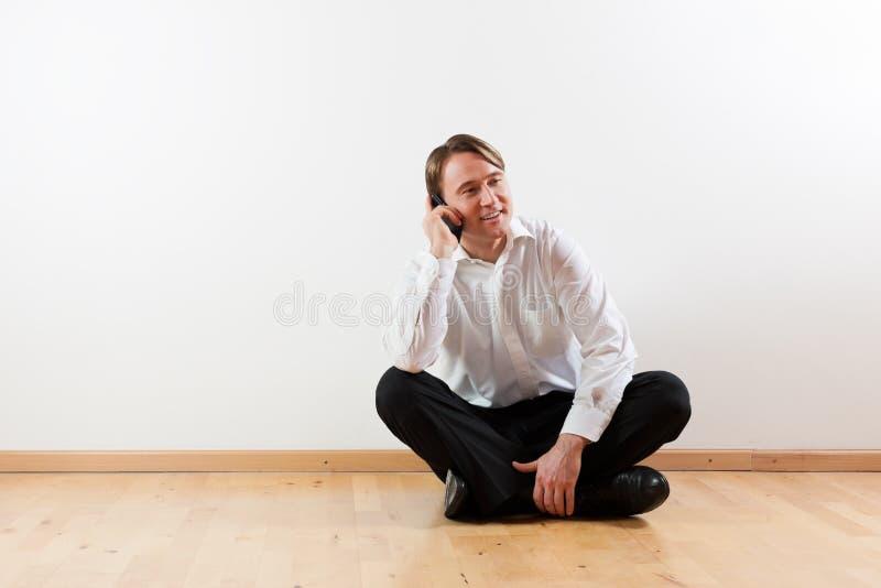 Uomo con il mobile in suo appartamento immagine stock libera da diritti