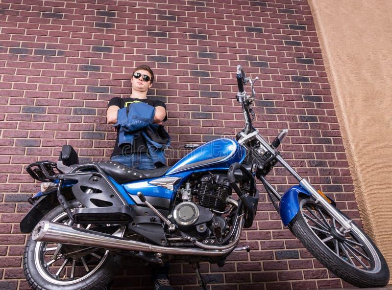 Uomo con il motociclo che pende contro il muro di mattoni fotografia stock