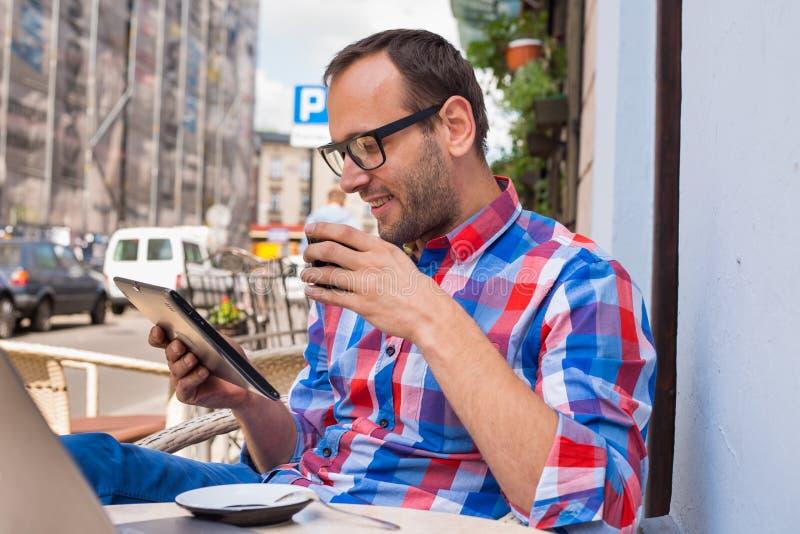 Uomo con il pc della compressa in caffè. Sta bevendo il caffè. immagini stock libere da diritti