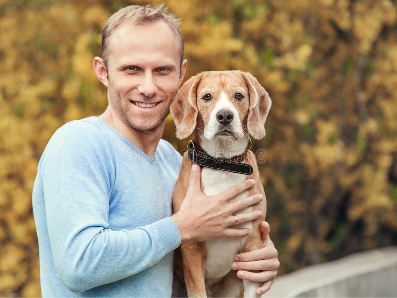 Uomo con il ritratto bello dell'animale domestico del cane del cane da lepre del favorit fotografia stock libera da diritti