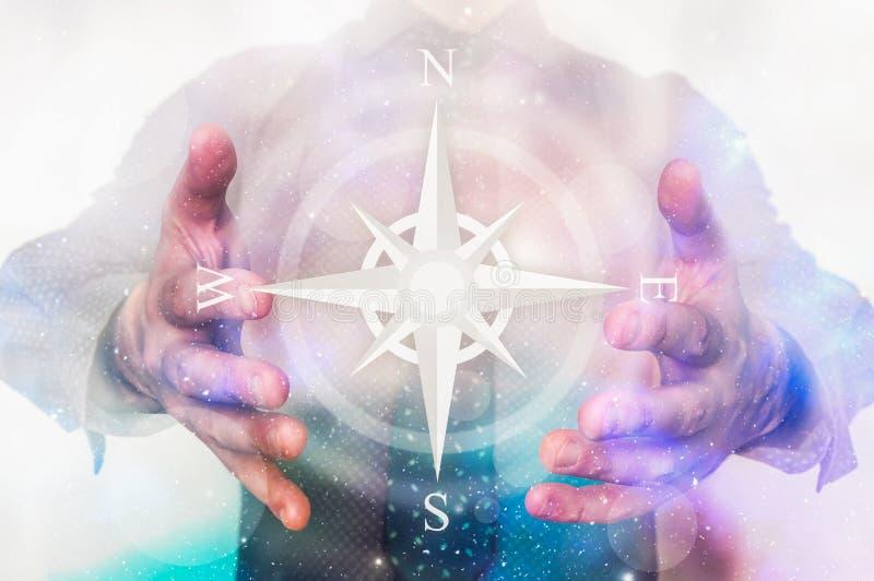 Uomo con il simbolo della bussola in sue mani magiche immagini stock libere da diritti