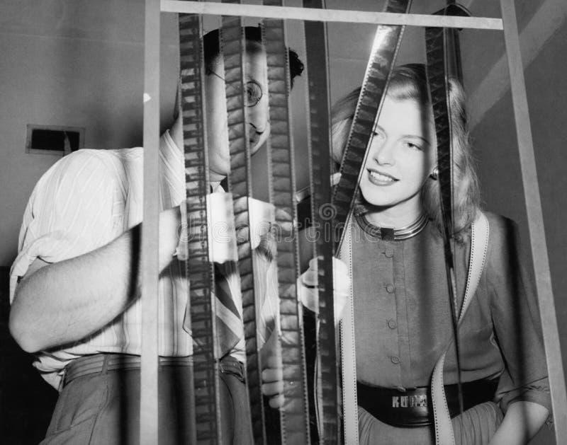 Uomo con il suo assistente che esamina le bobine di film (tutte le persone rappresentate non sono vivente più lungo e nessuna pro immagini stock libere da diritti