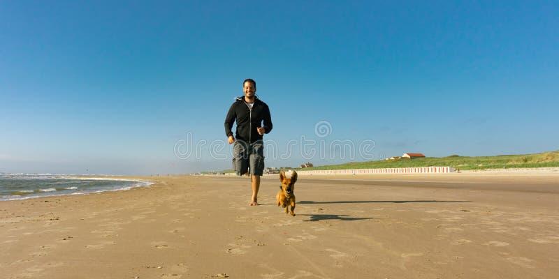 Uomo con il suo piccolo cane sveglio che corre alla spiaggia fotografia stock