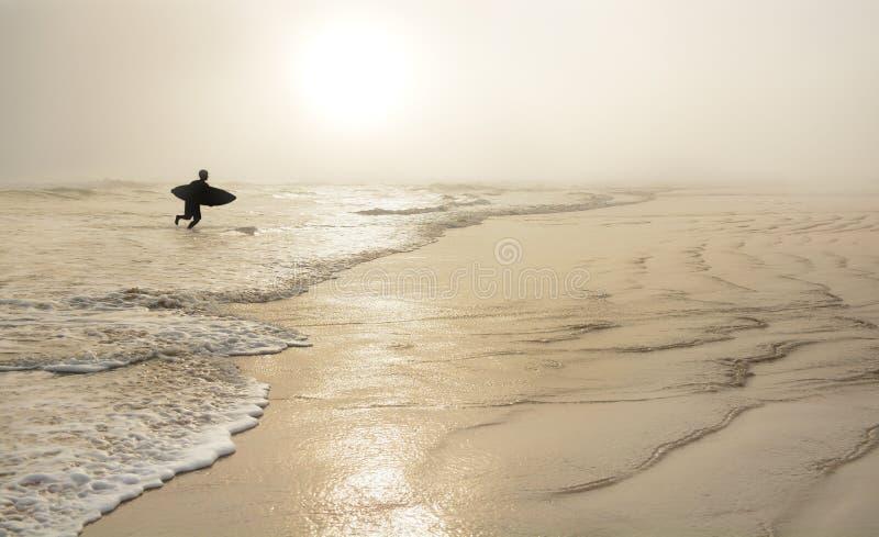 Uomo con il surf sulla bella spiaggia nebbiosa fotografia stock