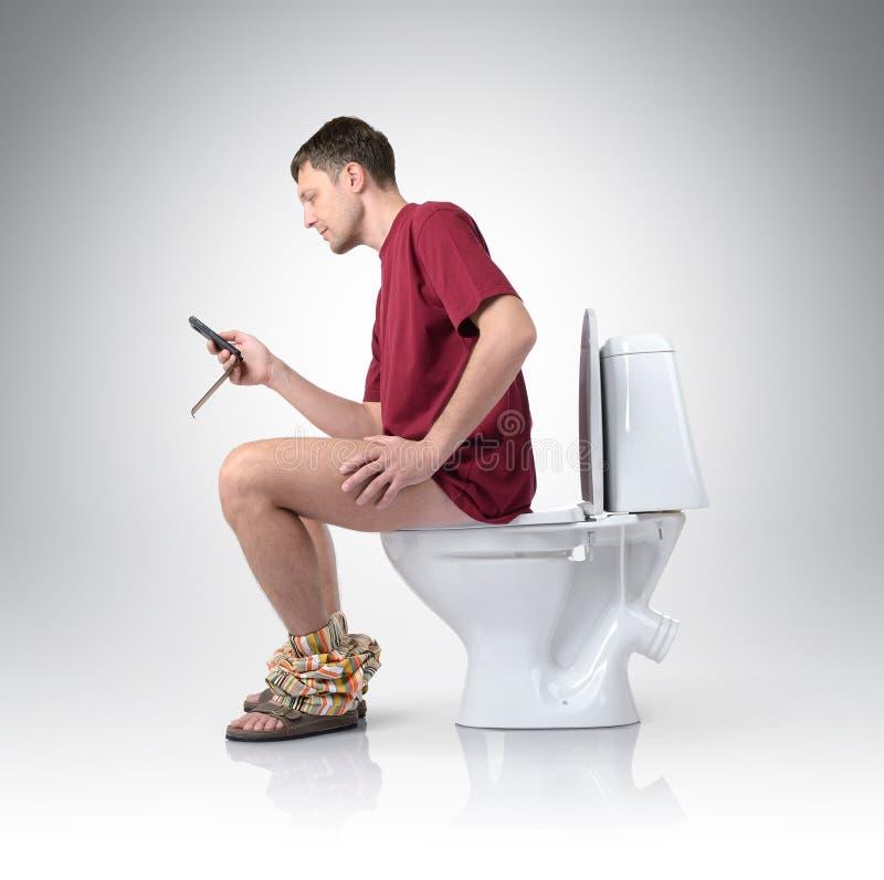 Uomo con il telefono cellulare che si siede sulla toilette fotografia stock libera da diritti