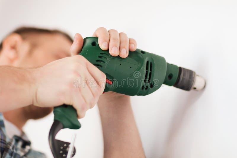 Uomo con il trapano elettrico che fa foro in parete fotografia stock libera da diritti