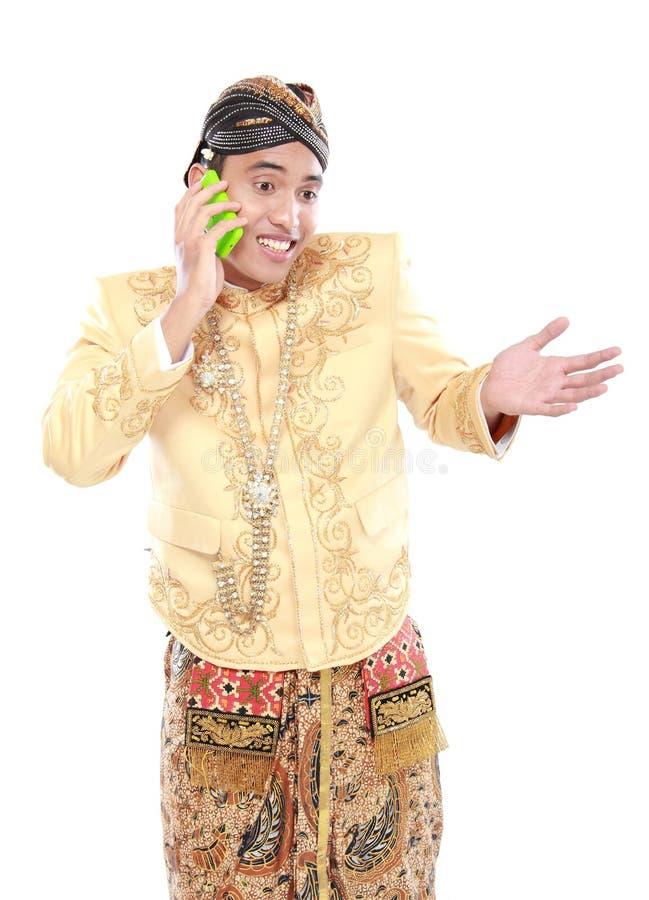 Download Uomo Con Il Vestito Tradizionale Di Java Facendo Uso Del Telefono Cellulare Fotografia Stock - Immagine di javanese, media: 30829756